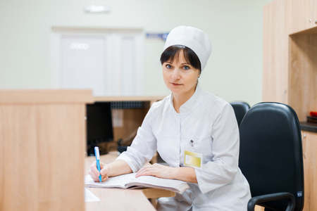 A female nurse in a white medical gown sits at a wooden desk at the reception desk and makes entries in a work log. Woman doctor working