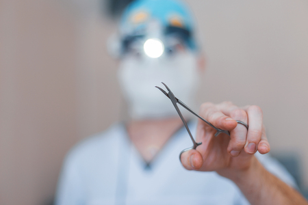 Surgeon in special medical clothes holds surgical metal scissors in his hand. Focus on the instrument. Operation process Close-up. 写真素材