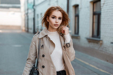 Pretty beautiful young woman in a stylish spring coat in a white T-shirt with a black leather bag walks around the city against the background of a white brick building. Banco de Imagens