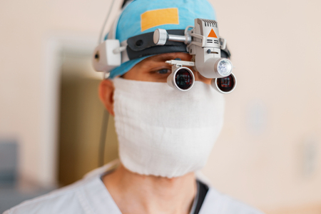 neurosurgeon man in a white mask in special medical clothes in magnifying glasses with binocular loupes is in a hospital. Surgical glasses. Medical equipment 写真素材