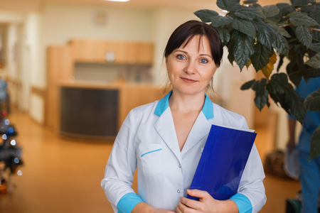 Young woman doctor in medical white clothes with a folder for documents standing in the hospital.