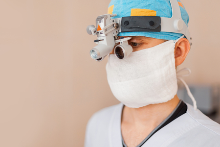 Young surgeon man in a white coat with professional magnifying glasses with binary loupes for microsurgery. Surgical operation with modern equipment