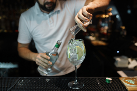 Man bartender makes a delicious cocktail with the addition of white wine, ice cubes and apple slices on a dark background. Lifestyle nightclub
