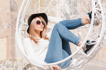 Stylish attractive young hipster woman in an elegant black hat in a white knitted sweater in stylish jeans in fashionable sneakers in sunglasses is sitting on a vintage iron white hanging chair. Cute