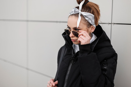 Beautiful hipster young woman with a fashionable hairstyle with a stylish bandana in black sunglasses in a trendy black jacket poses near the wall on a winter warm day. American girl in for a walk. Stock Photo