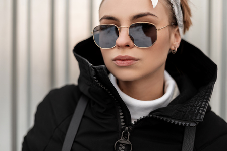 Portrait of a sexy hipster young woman in stylish sunglasses in a bandana in a fashionable winter jacket near a gray metal wall. American girl.