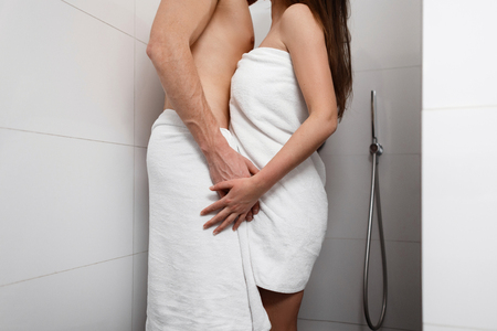 Handsome man with pretty woman standing in the shower and hugging. Young couple love and kiss. 版權商用圖片 - 117361889