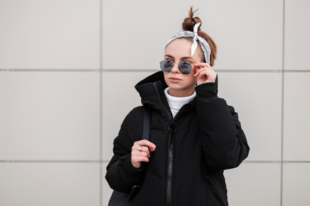 Beautiful fashionable young woman hipster with a stylish hairstyle in black glasses in a stylish black coat with a bandana with a black backpack on her shoulders posing near the wall. American girl.
