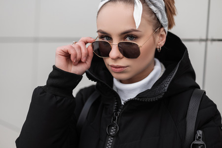 Portrait of a beautiful stylish young woman hipster with beautiful eyes with a fashionable hairstyle in stylish sunglasses in a knitted golf in a winter jacket near a white wall. Amazing girl.