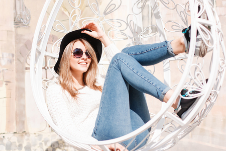 Funny happy young hipster woman in blue jeans in a knitted sweater in a fashionable hat in round sunglasses on a summer sunny day. Happy girl resting on a white suspended vintage chair. Banco de Imagens - 117390437