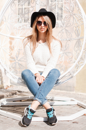 Young stylish hipster woman in sunglasses in fashionable spring clothes is sitting on a metal vintage chair on a sunny warm day. European girl resting.