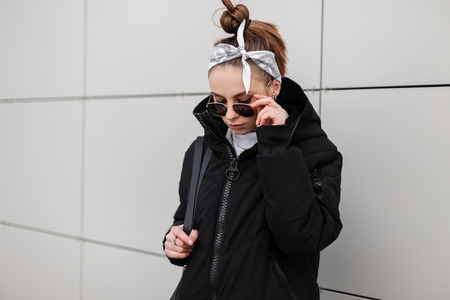 Modern young hipster woman with stylish hairstyle in a bandana in a fashionable black jacket with a stylish backpack in a knitted golf in stylish sunglasses posing near a white building. Fashion girl.