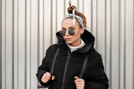 Young attractive hipster woman with stylish hairstyle with a bandana in black glasses in a long black coat with a backpack on her shoulders posing near a metal wall. Stylish girl. Stock Photo