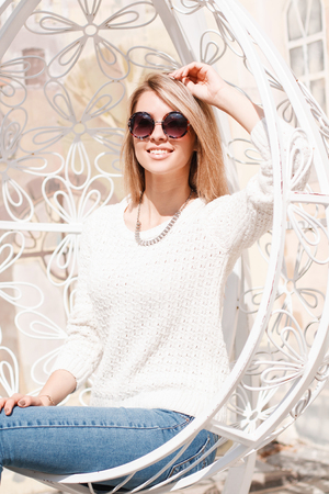 Happy cute young hipster woman in a knitted sweater in stylish jeans with black round sunglasses sits and smiles in a hanging beautiful metal chair. Charming cheerful girl resting.