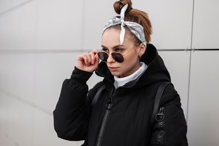 Portrait of a stylish young woman hipster with beautiful eyes with a fashionable hairstyle with a bandana in stylish sunglasses in a knitted golf in a winter jacket near a white wall. Amazing girl.