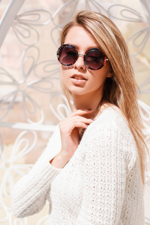 Portrait of an attractive hipster young woman in a fashionable vintage sweater in round stylish sunglasses on a white background. European modern beautiful girl. Stok Fotoğraf - 117391129