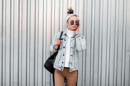 Cool modern young hipster woman in a bandana in a summer denim jacket in a knitted white vintage sweater in beige pants with a black handbag in sunglasses near the gray metal wall. Girl on vacation.