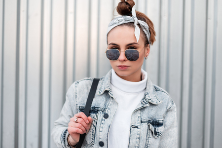 Portrait of young hipster woman in fashionable sunglasses with a stylish hairstyle in a knitted white vintage sweater in a denim jacket with a black backpack near a metal wall. American modern girl.