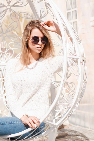 Pretty young hipster woman in fashionable blue jeans in a knitted white sweater in sunglasses is sitting in a metal beautiful vintage chair on a sunny warm day. Charming girl model. Banco de Imagens