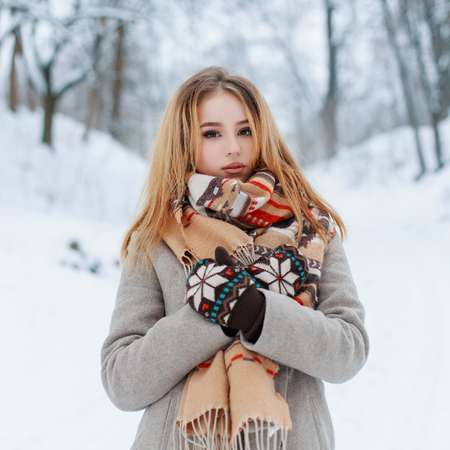 Modern charming young girl in a vintage warm coat in beautiful woolen mittens with a fashionable scarf with a red pattern posing outdoors on the background of snowy trees in the park. Stylish girl.