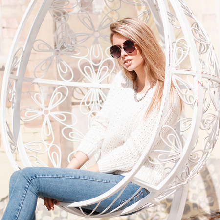 Attractive happy young hipster woman in blue jeans in a knitted sweater in sunglasses is sitting in an iron white vintage hanging chair in outdoors. Joyful girl enjoying the sun. Banco de Imagens - 117393047