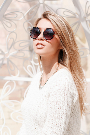 Sensual young hipster woman in trendy sunglasses in a knitted white sweater enjoys the summer warm sunlight in outdoors. Beautiful cute girl.
