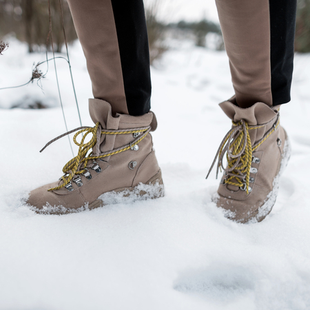 Womans legs in stylish pants in winter brown leather fashion boots on snow. Close-up. Reklamní fotografie