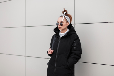 Modern young hipster woman in round sunglasses in a stylish coat in a fashionable bandana with a leather backpack is standing near a white wall a warm winter day. Fashionable american girl on vacation