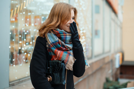Positive young woman in a winter black coat in stylish gloves with a leather handbag with a woolen scarf is standing and laughing near the shop window decorated with festoons. Good mood. Cute girl. Zdjęcie Seryjne