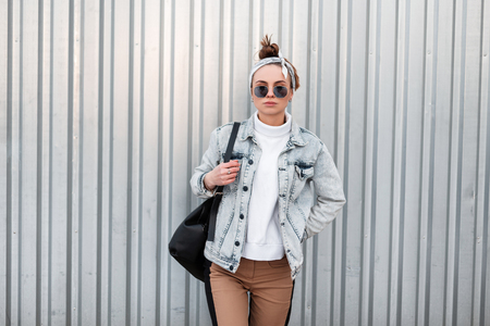 American hipster young woman with a stylish hairstyle in summer denim jackets in trendy pants in a knitted white sweater in sunglasses with a bandana near a shiny gray metal wall. Modern girl. Stock Photo