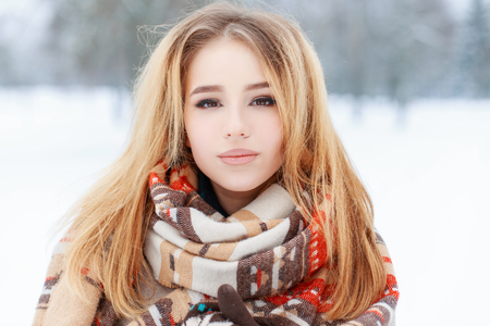 Portrait of a pretty young woman with brown eyes with beautiful makeup  with long blond hair in a woolen vintage warm scarf in a snowy park. Cute girl on a walk.