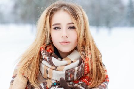 Portret van een mooie jonge vrouw met bruine ogen met mooie make-up met lang blond haar in een wollen vintage warme sjaal in een besneeuwd park. Leuk meisje op een wandeling.