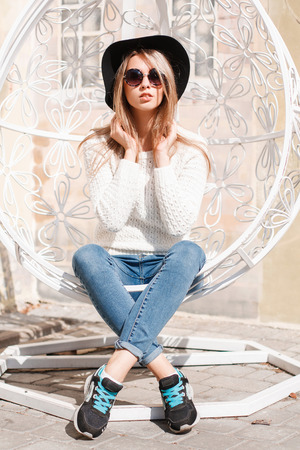Beautiful attractive young hipster woman in a black hat in a stylish knitted sweater in blue jeans in black sneakers in round sunglasses posing on a vintage iron white hanging chair. Cool girl.