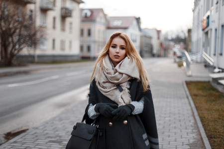 Fashionable attractive young blond woman in a vintage knitted sweater in a stylish coat in warm gloves with a vintage scarf with a fashionable black leather bag walking on the street. City cute girl. Standard-Bild