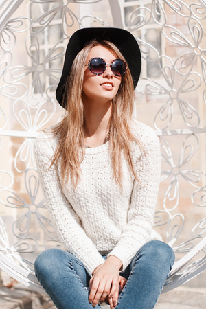 Attractive happy young hipster woman in an elegant hat in blue jeans in a knitted sweater in sunglasses posing sitting in an iron white vintage hanging chair outdoors. Joyful girl enjoys the sun. Banco de Imagens