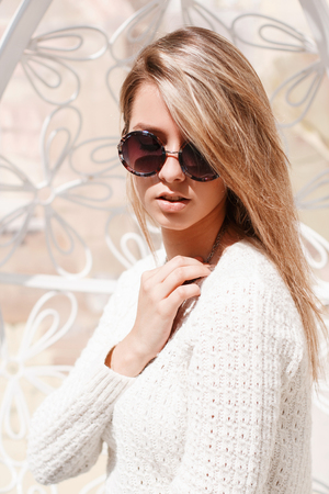 Portrait of a sexy feminine young hipster women in round sunglasses in a knitted white sweater with white hair near a metalic vintage white wall. Charming sweet girl enjoying the spring sun.