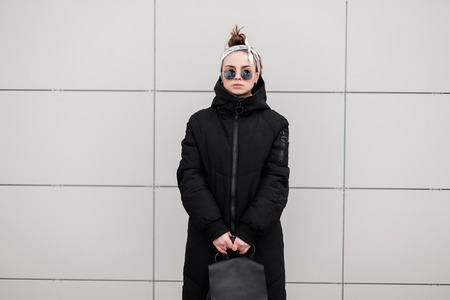 Stylish hipster young woman in stylish sunglasses in a bandana in a fashionable long jacket with a leather stylish backpack near a white wall. American modern girl. Women's fashion.