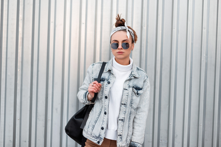 Stylish young hipster woman in sunglasses in trendy bandana in summer denim jackets in a knitted sweater with a black leather backpack on a warm summer day stands near a shiny metal wall. Cool girl. Stock Photo