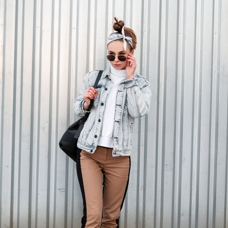 Young hipster girl in trendy clothes in trendy bandana with a stylish hairstyle in sunglasses with a handbag in a knitted sweater near a metal building. American girl. Summer style women's clothing.