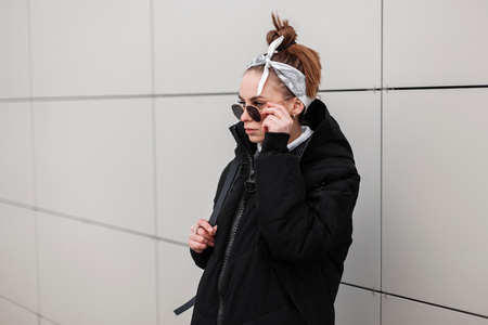 Young woman hipster in a stylish long jacket with a leather backpack with a stylish hairstyle in a trendy bandana in black sunglasses near a white wall in the outdoors. American girl. Modern fashion. Stock Photo