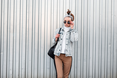Cute young woman hipster with a stylish hairstyle in a trendy bandana in a knitted vintage sweater in a denim jacket in stylish pants with a black backpack stands near a metal wall. Girl for a walk.