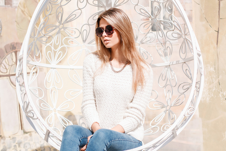 European stylish young woman hipster in sunglasses with a brilliant necklace in stylish jeans in a knitted sweater sits in a vintage metal white hanging chair. Happy girl enjoys the sun. Banco de Imagens