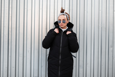 American beautiful young hipster woman in a winter stylish black coat with a leather backpack with a bandana in sunglasses near a metal building. Nice girl on a walk. Stock Photo