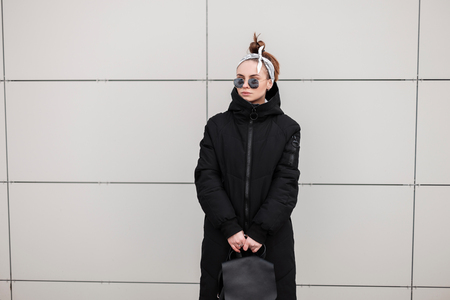 American fashionable young hipster woman in a long winter stylish black coat with a leather backpack with a bandana in sunglasses near a modern building. Trendy girl on a walk. Stock Photo