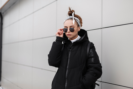 Modern fashionable young woman hipster with stylish hairstyle in black glasses in a stylish long black coat with a bandana with a leather backpack on her shoulders posing near the wall. American girl. Stock Photo