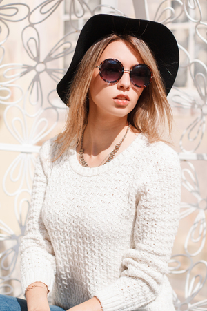 Beautiful hipster young woman in fashionable sunglasses in a knitted white sweater in blue jeans in an elegant hat sits and rests in a hanging vintage metal white chair. Charming girl. Banco de Imagens