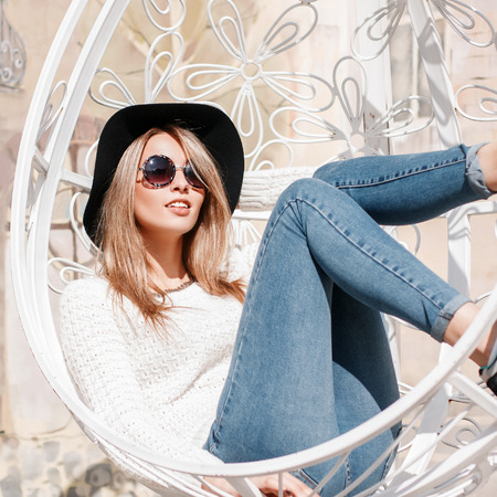 European stylish young woman hipster in sunglasses in a luxurious hat in stylish jeans in a knitted sweater in sneakers lies in a vintage metal white hanging chair. Happy girl enjoys the sun. Banco de Imagens