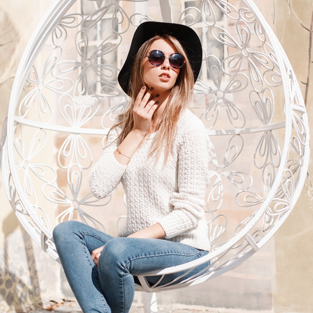 Fashionable young hipster woman in round sunglasses in a knitted vintage sweater in blue jeans in an elegant black hat sits and rests in a hanging vintage metal white chair. European modern girl.