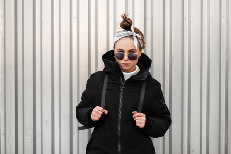Young fashionable beautiful hipster woman with a stylish hairstyle with a bandana in black sunglasses in a long black coat with a backpack on her shoulders poses near a metal wall. Modern stylish girl
