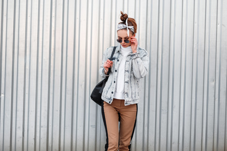 Young attractive hipster woman in knitted vintage white sweater in beige pants in a denim jacket in a bandana with a black backpack posing outdoors near a metal building. Cool girl. Women's fashion.